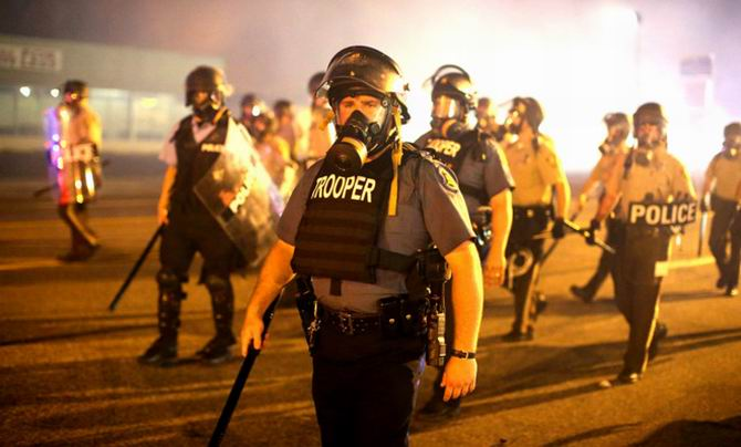 heavily-armed-police-advance-through-a-cloud-of-tear-gas-during-protests-in-ferguson-missouri.jpg